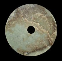 AN EXCEPTIONALLY LARGE PALE GREEN AND RUSSET JADE BI DISC, EARLY BRONZE AGE