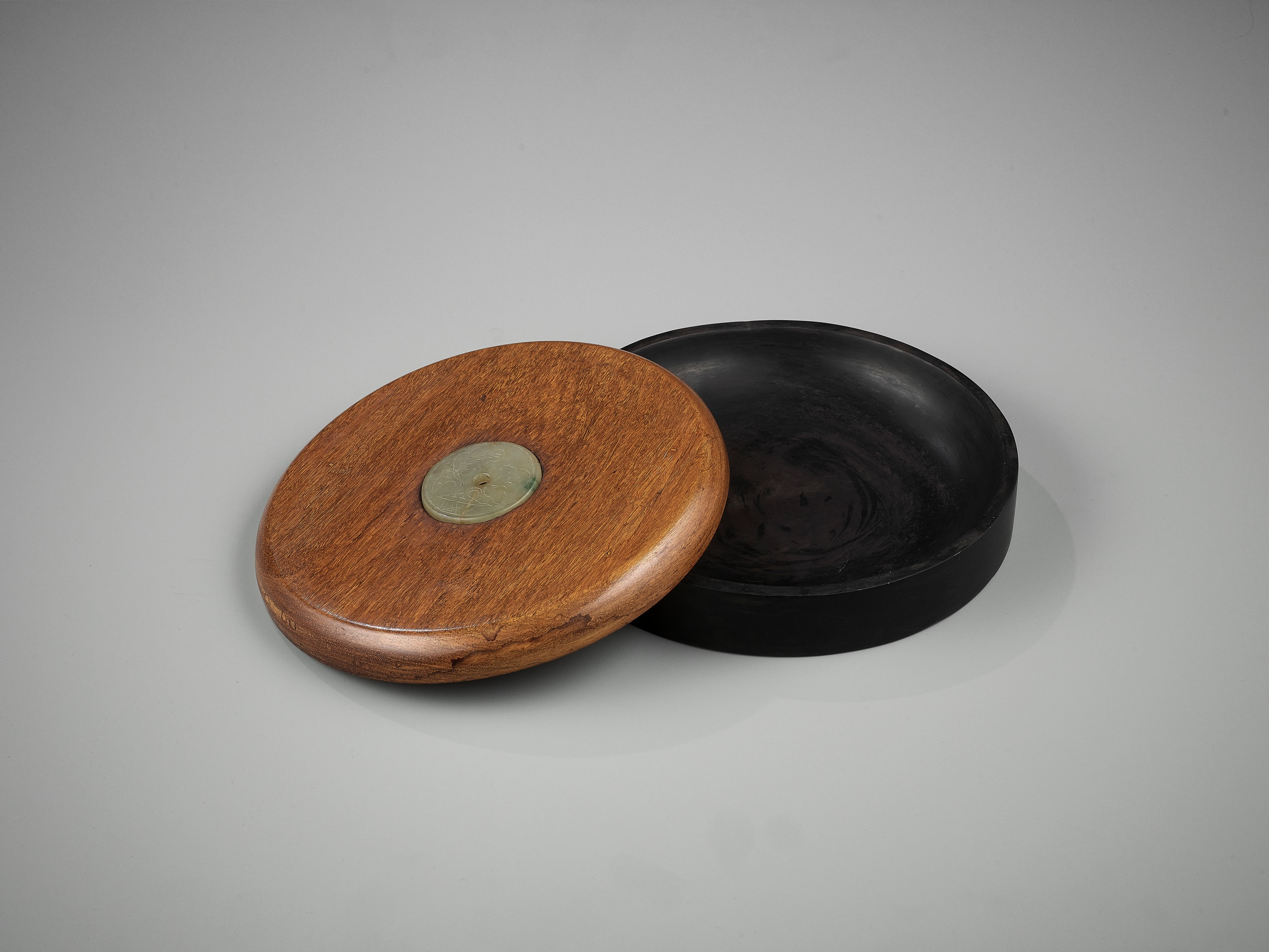 A DUAN INKSTONE WITH A JADEITE-INSET HUANGHUALI COVER, QING