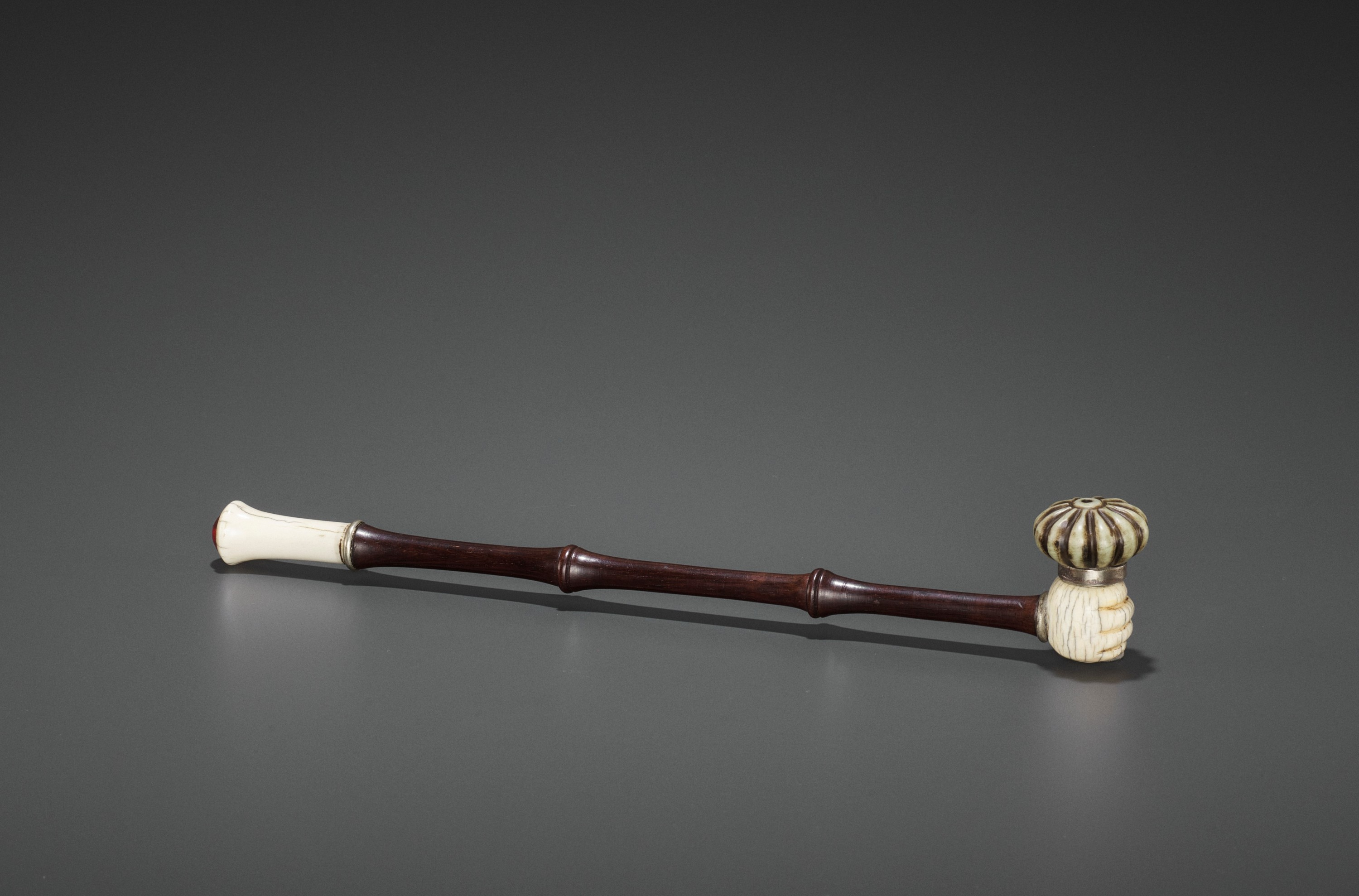 A HARDWOOD OPIUM PIPE WITH IVORY, HARDSTONE AND SILVERED COPPER FITTINGS, LATE QING TO REPUBLIC
