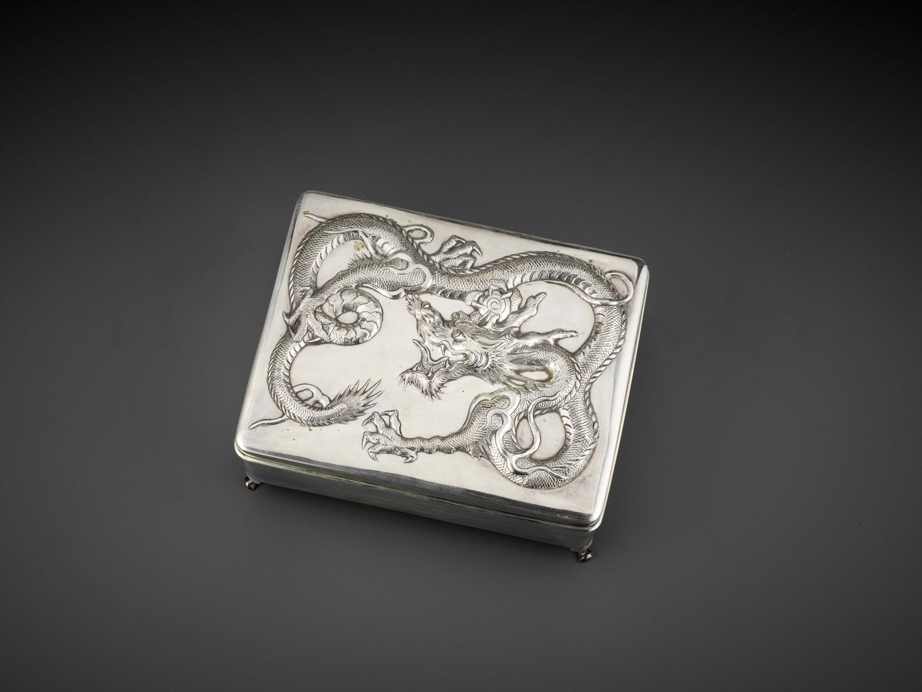 A SILVER REPOUSSE 'DRAGON' BOX AND COVER, WANG HING, LATE QING TO REPUBLIC