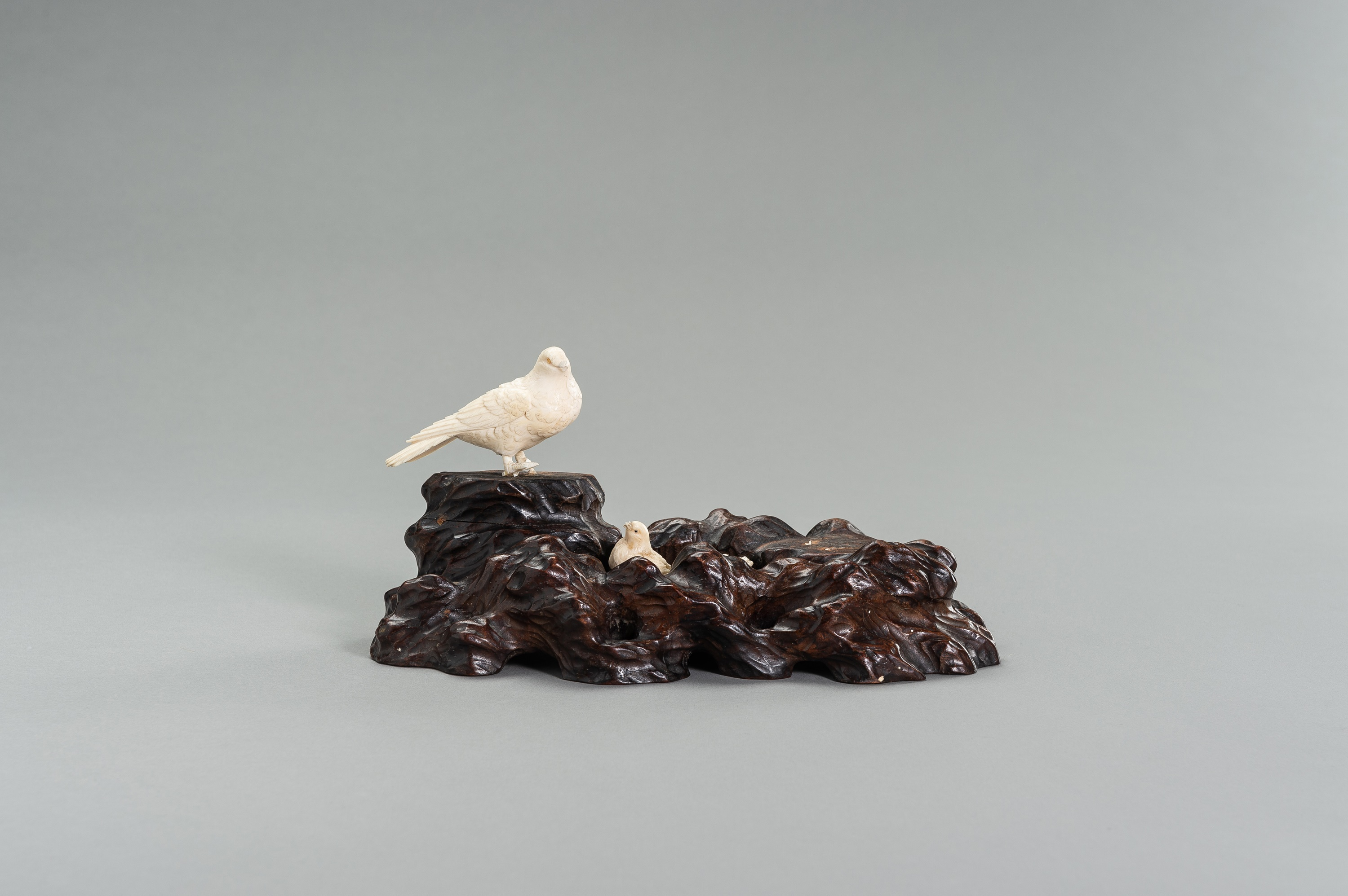 AN IVORY OKIMONO GROUP OF A COUPLE OF BIRDS WITH CHICKS