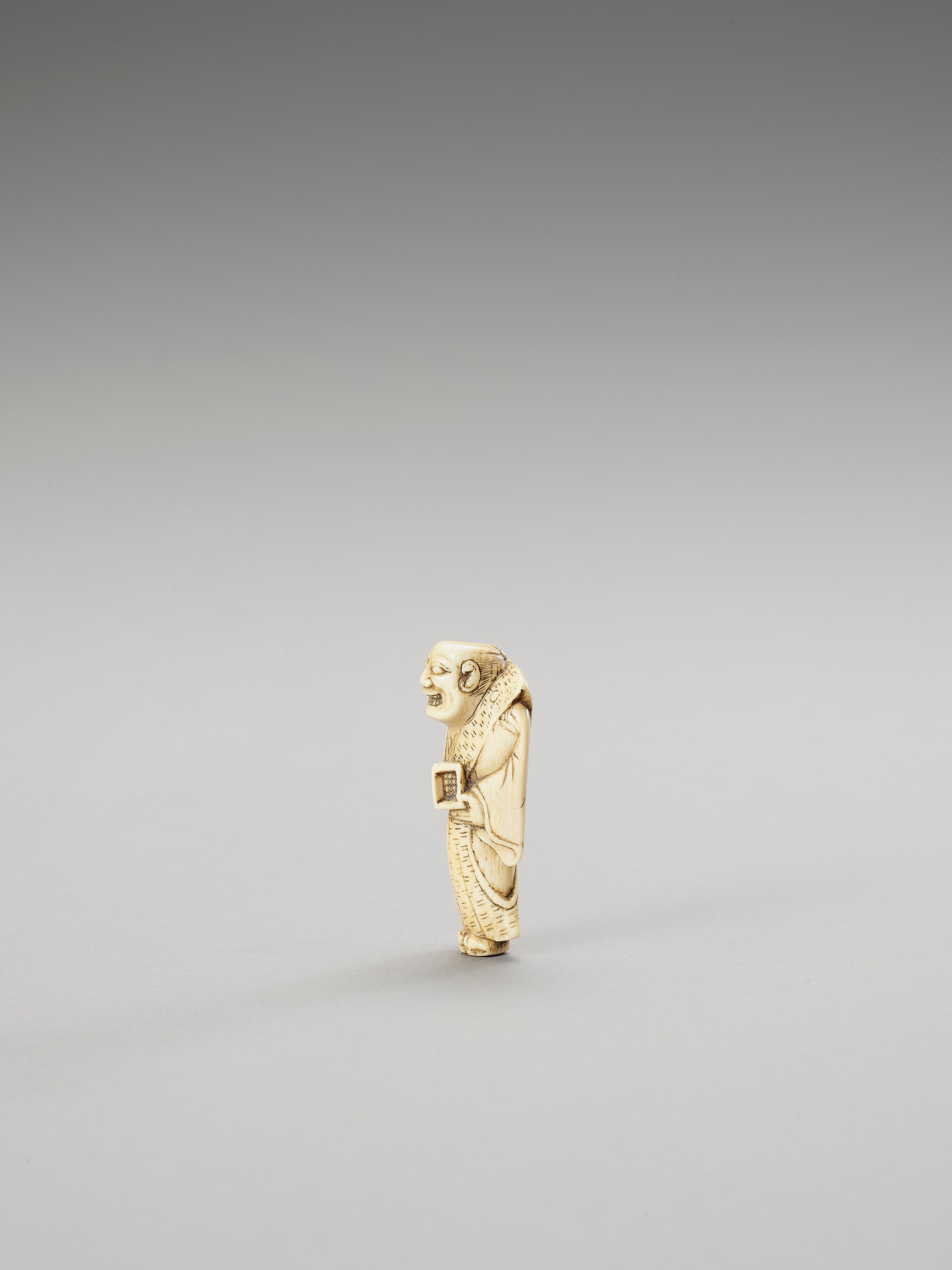 AN IVORY NETSUKE OF A MAN THROWING ROASTED BEANS - Image 2 of 3