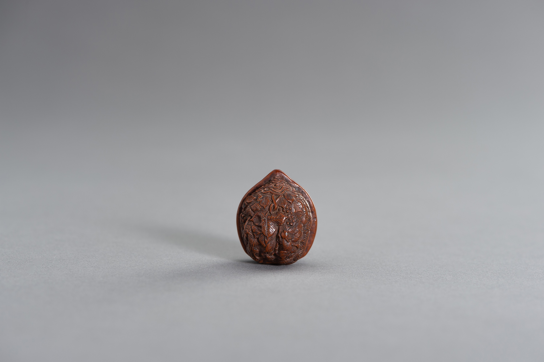 A KURUMI (WALNUT) NETSUKE OF GRAPEVINE AND SMALL ANIMALS