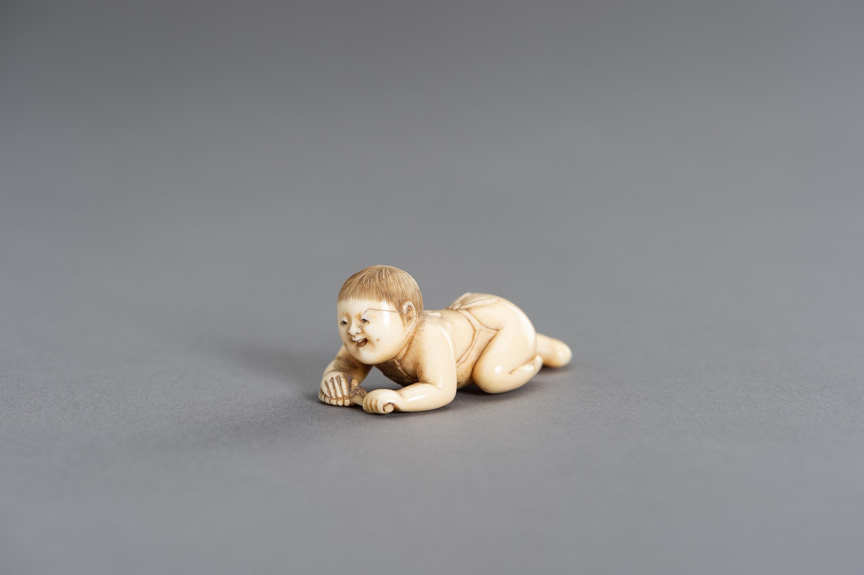 MASATSUGU: A FINE IVORY NETSUKE OF A CRAWLING INFANT