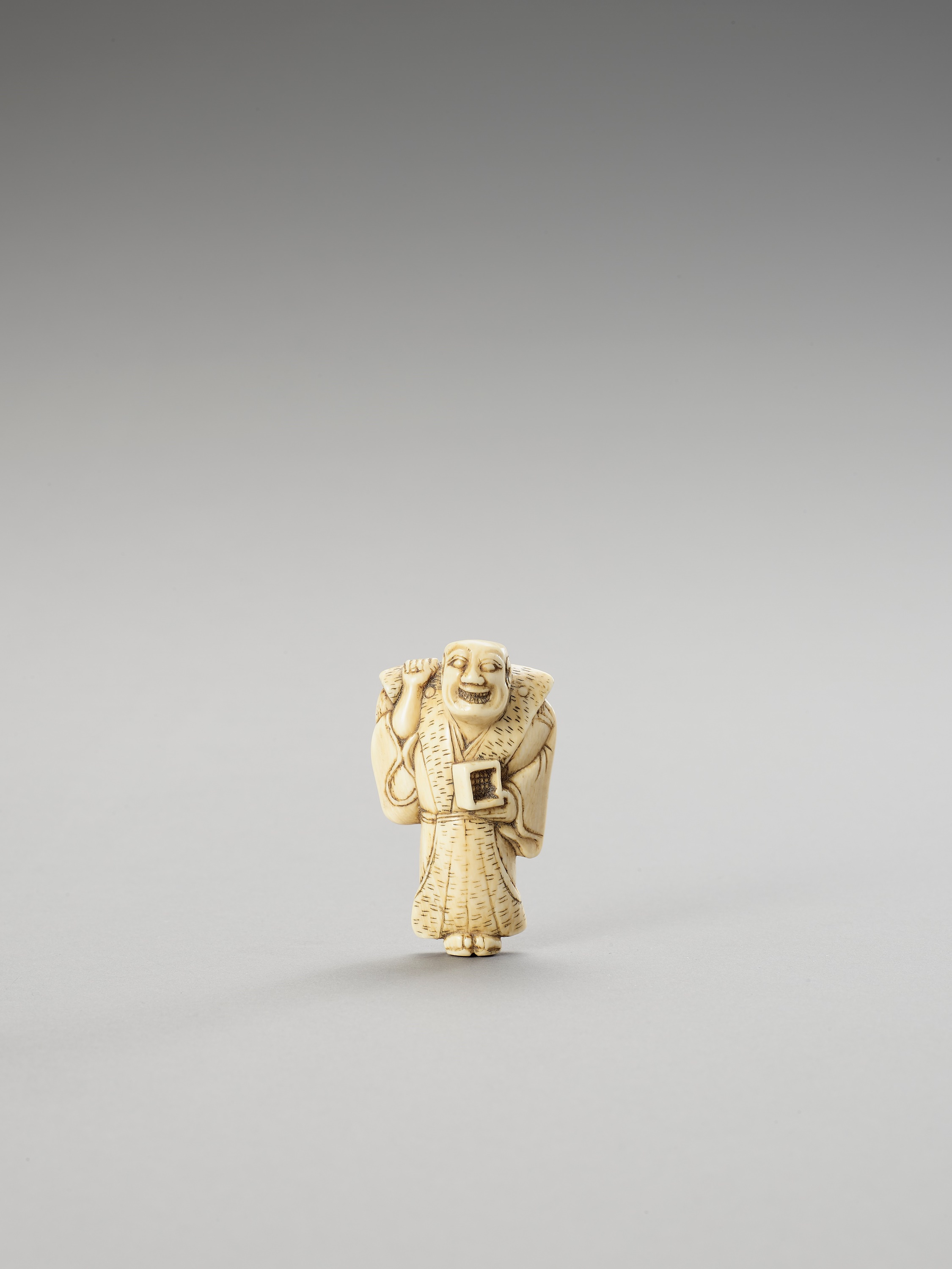 AN IVORY NETSUKE OF A MAN THROWING ROASTED BEANS