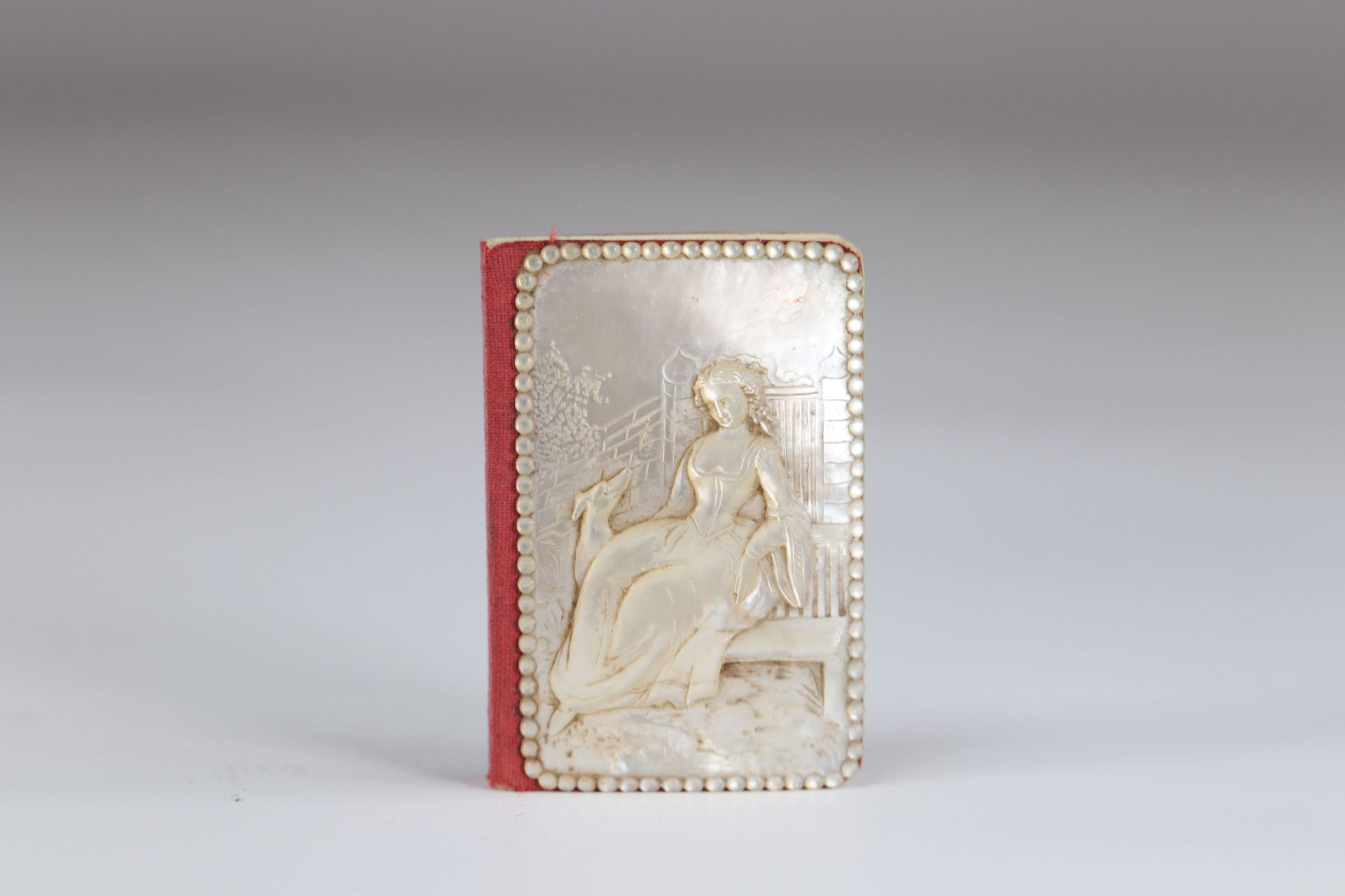 Carved mother-of-pearl ball book of a young woman with a greyhound