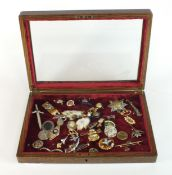 A selection of military-related badges, brooches and jewellery