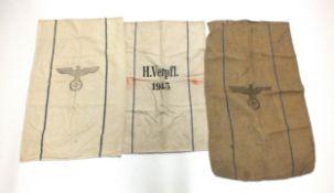 Three German Second World War grain sacks, the cloth sacks with eagle atop a swastika, variously