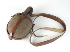 A German Mountain Troops field canteen with brown leather straps and black cup, also used by