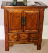 A Chinese elm collectors cabinet, moulded oversailing top, above two panel cupboards over three