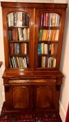 A Victorian mahogany library bookcase, circa 1860, slight oversailing pediment, above arch shaped
