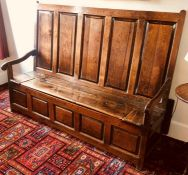 A George III joined oak settle, circa 1770, the back support with five moulded panels above a hinged