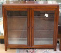 An early 20th Century mahogany glazed bookcase, circa 1910, fitted with two doors enclosing shelves,