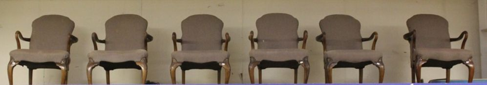 A set of six walnut dining armchairs, in the George I style, having upholstered backs and seats,