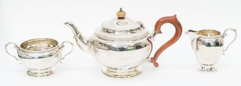 A George VI three piece silver tea service comprising teapot, milk jug and sugar bowl, plain