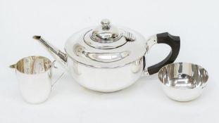 A George V plain circular silver matched three piece tea service comprising teapot, sugar bowl and