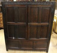 A late 17th Century joined oak clothes press, lunette carved frieze and bearing the initials 'EB',