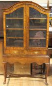A Queen Anne style walnut glazed bookcase, dome topped, fitted with two glazed doors enclosing three