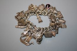 A 20th century silver charm bracelet affixed with 33 charms: dolphin, tennis racket, thimble,