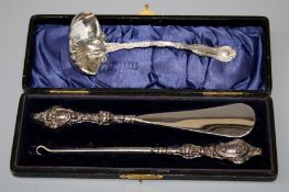 An American Sterling silver sauce ladle, together with a presentation cased button hook and shoe
