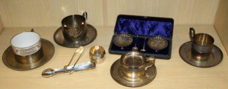Three French white metal tea cups and saucers, one decorated in shallow relief with mistletoe,