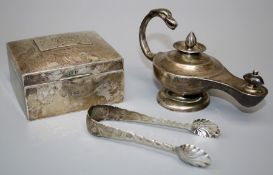 A silver lamp form table lighter, a silver cigarette box and a pair of sugar nips. Various dates and