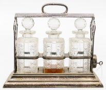 **WITHDRAWN** An Edwardian silver-plated three bottle tantalus, by Walker and Hall, with key