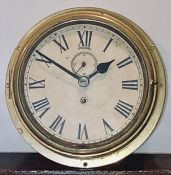 An early 20th century brass ship clock, circa 1920, circular form with roman numerals and subsidiary