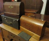A group of three sewing machines, two Singers (one with original mat) in wooden cases and one in a