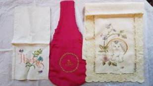 A small linen handkerchief case with handkerchiefs, embroidered in pink and a sprig of foliage and