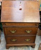A Georgian oak bureau, of small proportions, the later replaced fall front enclosing drawers and