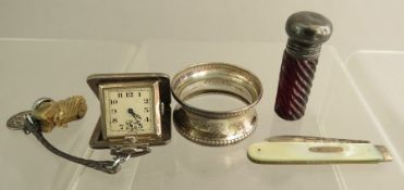 A small group of silver items: a napkin ring, scent bottle, a penknife with mother of pearl