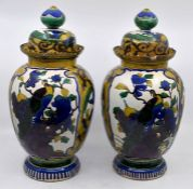 A pair of 20th century Japanese style ovoid vases and covers, painted with fanciful birds and trees,