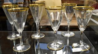 A pair of Edwardian glass ewers, gilt line detail; and a set of six wine glasses (8)