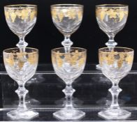 A set of six faceted crystal wine glasses, gilt vine decoration, hexagonal bases (6)