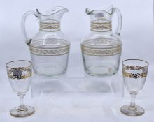 A pair of late 19th/early 20th century glass jugs, with gilt borders; and a pair of wine glasses (