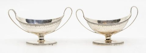 A pair of George III silver twin handled boat shaped condiments, beaded borders and bright cut