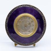 A George V silver circular easel desk or bedside timepiece, purple guilloche enamel frame in a black