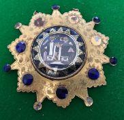 A George III gilt metal Masonic badge, the mount of sunburst form bright cut engraved foliage