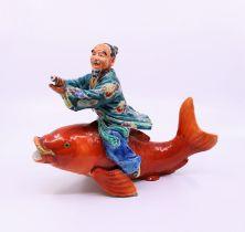 A Japanese pottery fisherman straddling a carp