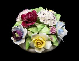 A Royal Doulton china table decoration modelled as a flowers pot with bouquet of flowers in relief,