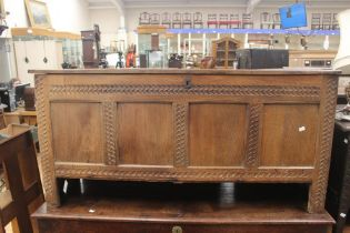 A traditional oak chest, possibly 17th Century, having a four panelled front, plank lid, chip