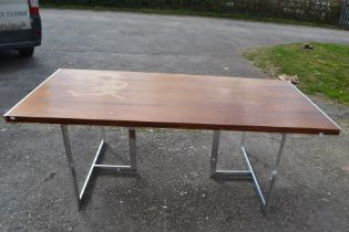 A Scandinavian rosewood refectory table raised on a pair of chrome tripod supports. 71cm H x 199cm W