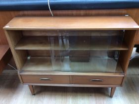 A mid 20th Century teak glazed bookcase, fitted with two glass sliding doors, two drawers to base