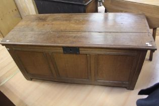 A late 17th / early 18th Century joined oak chest, circa 1700, having a plank lid, three panels to