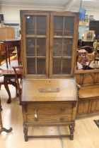 An early 20th Century oak bureau bookcase, fitted with two doors enclosing wooden shelves, the