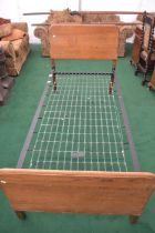 A Plycene Utility oak framed single bed frame, with back and foreboards