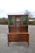 An Art Nouveau oak sideboard, circa 1910, with glazed upper section fitted with stained glass doors,