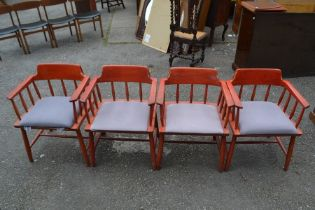 A set of four mid 20th Century red stained armchairs, each with rodded backs and arm supports,