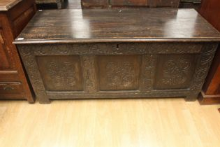 An early 18th Century joined oak coffer, having a three panelled front, carved plank top, 63cm high,